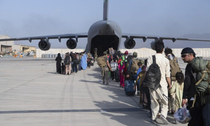 In this image provided by the U.S. Air Force, U.S. Air Force loadmasters and pilots, assigned to the 816th Expeditionary Airlift Squadron, load people being evacuated from Afghanistan onto a U.S. Air Force C-17 Globemaster III at Hamid Karzai International Airport in Kabul, Afghanistan, on Aug. 24, 2021. (Master Sgt. Donald R. Allen/U.S. Air Force via AP)