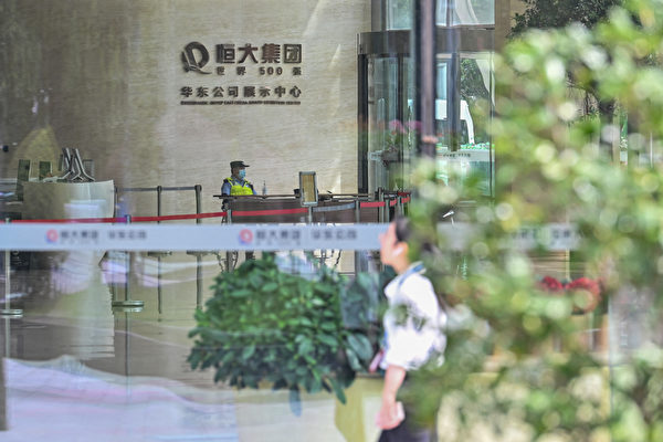 A police officer is seen at the lobby of the Evergrande Center building in Shanghai on Sept. 24, 2021. (Hector Retamal/AFP via Getty Images)