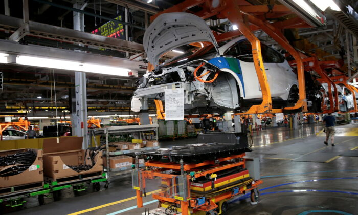 An automated guided vehicle carrying a battery pack moves under a partially assembled 2018 Chevrolet Bolt EV vehicle on the assembly line at General Motors Orion Assembly in Lake Orion, Mich., on March 19, 2018. (Rebecca Cook/Reuters)