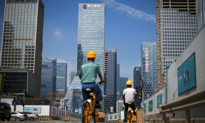 Men ride bicycles past construction sites near the headquarters of China's Evergrande Group in Shenzhen, Guangdong Province, China on Sept. 26, 2021. (Aly Song/Reuters)