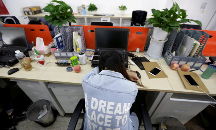 Yang Juan, an employee at Goopal Group, takes a nap in her seat after lunch, in Beijing, China, on April 21, 2016. (Jason Lee/Reuters)