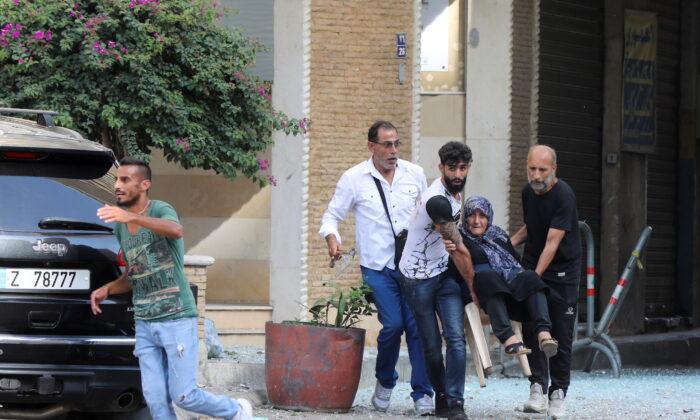 Men help evacuate an elderly woman after gunfire erupted, in Beirut, Lebanon, on Oct. 14, 2021. (Mohamed Azakir/Reuters)