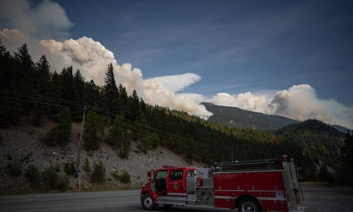 A man sits in a fire truck as the Lytton Creek wildfire burns in the mountains near Lytton, B.C., on August 15, 2021. (The Canadian Press/Darryl Dyck)