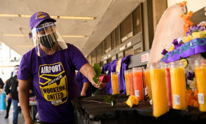 An airport worker in support of the Service Employees International Union (SEIU) leaves a flower at an altar as they protest and call on California Gov. Gavin Newsom to support vaccine priority for essential workers during the COVID-19 pandemic at Los Angeles International Airport (LAX) on Feb. 4, 2021. (Patrick T. Fallon/AFP via Getty Images)