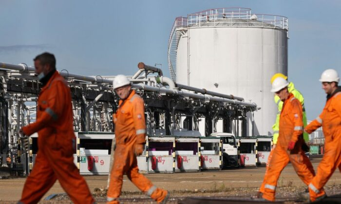 A tanker is stocked with fuel as workers walk past at the Hamble oil refinery near Southampton, England, on Oct. 4, 2021. (Adrian Dennis/AFP via Getty Images)