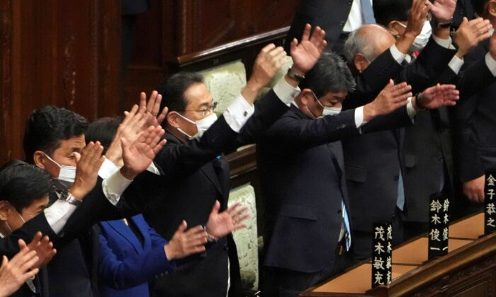 Japanese Prime Minister Fumio Kishida (C), and other lawmakers give three cheers after dissolving the lower house, the more powerful of the two parliamentary chambers, during an extraordinary Diet session at the lower house of parliament in Tokyo, on Oct. 14, 2021. (Eugene Hoshiko/AP Photo)