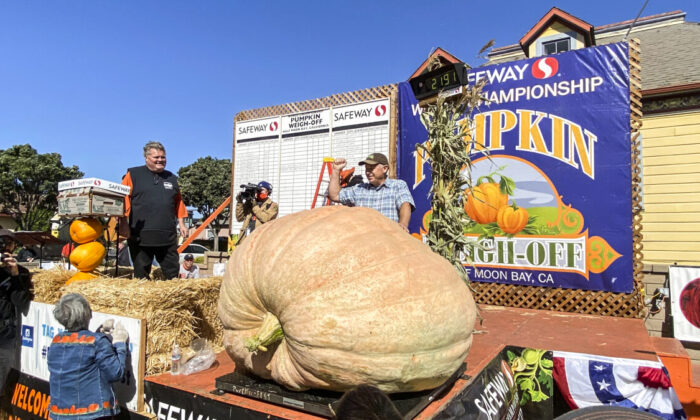 Jeff Uhlmeyer stands behind his 2,191-pound pumpkin, which won the 48th Safeway World Championship Pumpkin Weigh-Off at I.D.E.S. Portuguese Hall in Half Moon Bay on Oct. 11, 2021. (Ilene Eng/The Epoch Times)