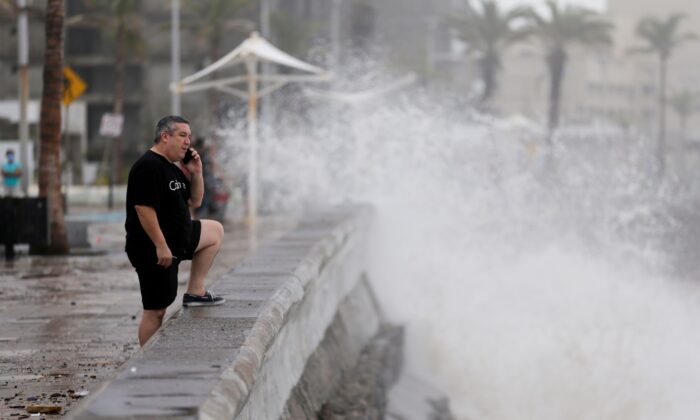A man speaks on his mobile phone as hurricane Pamela pounds the Pacific coast resort with strong winds as it makes landfall in Mazatlan, Mexico, on Oct. 13, 2021. (Daniel Becerril/Reuters)