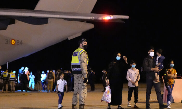 Afghan people who were transported from Islamabad walk after disembarking a plane, at the Torrejon military base in Spain on Oct. 11, 2021. (Manu Fernandez/AP Photo)