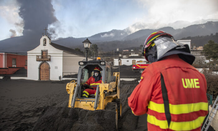Military Emergency Unit personal clear black ash from volcano as it continues to erupt lava behind a church on the Canary island of La Palma, Spain, on Oct. 13, 2021. (Saul Santos/AP Photo)