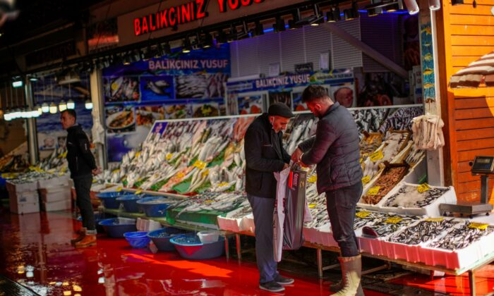 A fishmonger talks to a client at Karakoy fish market in Istanbul, Turkey,  on Oct. 14, 2021. (Francisco Seco/AP Photo)