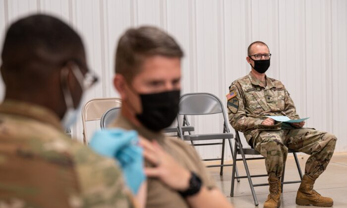 A soldier watches another soldier receive his COVID-19 vaccination in Fort Knox, Ky., on Sept. 9, 2021. (Jon Cherry/Getty Images)