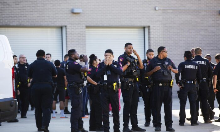 A Harris County Pct. 4 deputy covers his face after participating in a procession as the body of a fellow Harris County Pct. 4 deputy who was shot and killed in north Houston was transported to the facility, on Oct. 16, 2021. (Marie D. De Jesús/Houston Chronicle via AP)