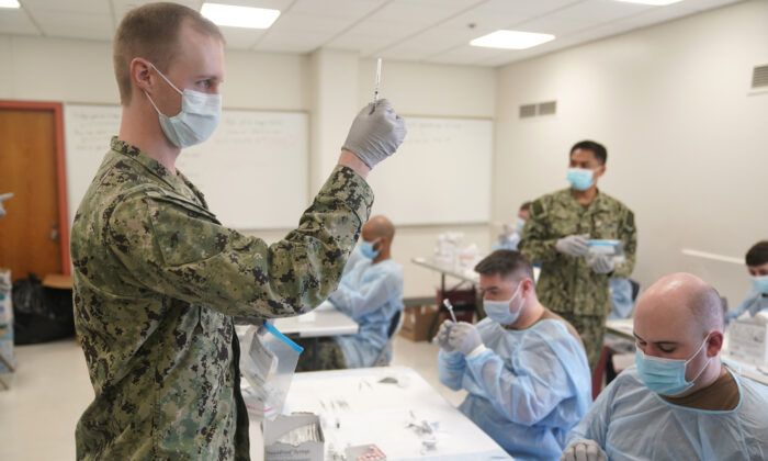 Navy personnel prepare doses of a COVID-19 vaccine at a vaccination site in New York City on Feb. 24, 2021. (Seth Wenig/Pool/AFP via Getty Images)
