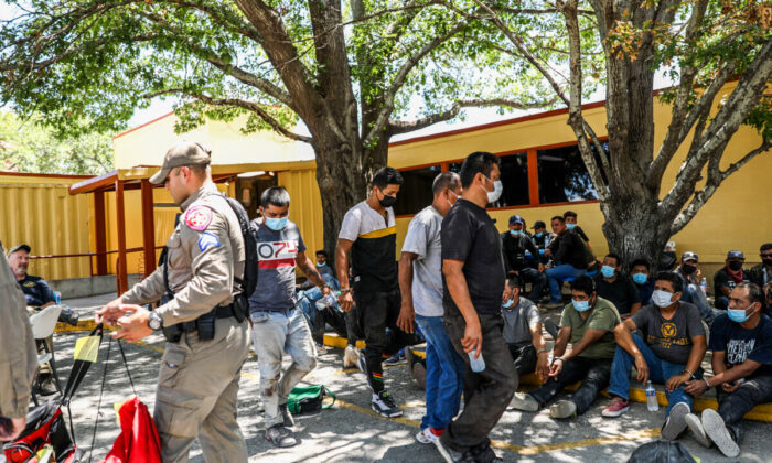 A total of 52 illegal immigrants from Mexico and Honduras wait to be booked for criminal trespass after being arrested by Texas State Troopers on local ranches, at the Kinney County Sheriffs Office in Brackettville, Texas, on Aug. 8, 2021. (Charlotte Cuthbertson/The Epoch Times)