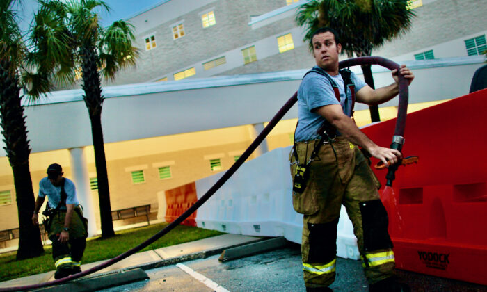 Orange County firemen use a hose to fill protective barriers with water in front of the booking and release center at the Orange County Jail July 15, 2011 in Orlando, Florida. (Joe Raedle/Getty Images)