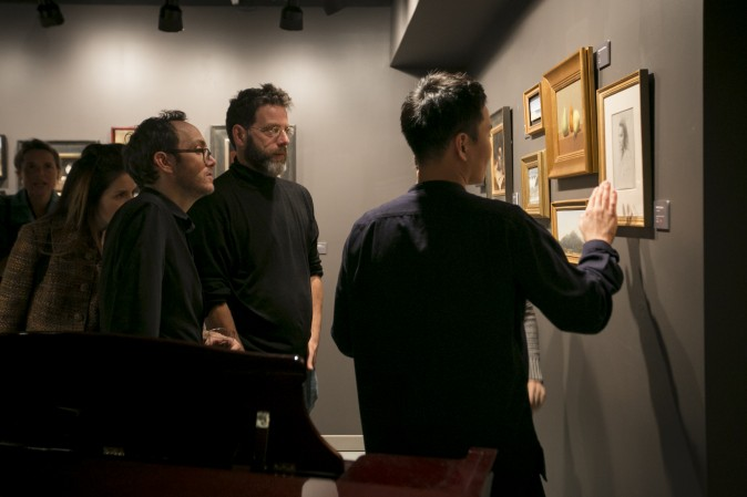 Artists, Dale Zinkowski (L) Patrick Byrnes (R) and founder of Grand Central Atelier, Jacob Collins (C), look at artwork at the opening of the Wrap Me Up: Winter Small Works Show at Eleventh Street Arts gallery in Long Island City, New York, on Nov. 17, 2016. (Samira Bouaou/Epoch Times)