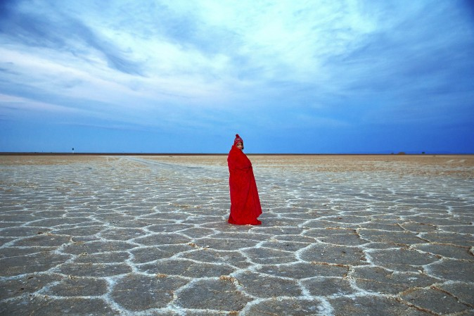 In this picture taken on Thursday, Dec. 1, 2016, an Iranian woman covers herself with a blanket due to the cold, while visiting Khour salt lake during her tour of the Mesr desert in Iran. Deserts make up parts of Iran which have recently become tourist destination for young Iranians looking for a break on their weekend. (AP Photo/Ebrahim Noroozi)