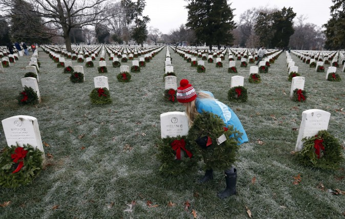 Madeline Espinosa, 11, places a wreath at a grave as part of Wreaths Across America at Arlington National Cemetery in Arlington, Va., on Dec. 17, 2016. Organizers estimate more than 245,000 wreaths were placed at graves throughout the cemetery. (AP Photo/Alex Brandon)