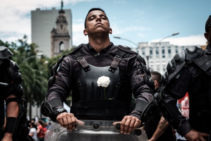A riot police officer bearing a white flower on his bulletproof vest takes part in a public servants' protest against austerity measures in front of the Rio de Janeiro state Assembly (ALERJ) in Brazil on Dec. 12. (YASUYOSHI CHIBA/AFP/Getty Images)