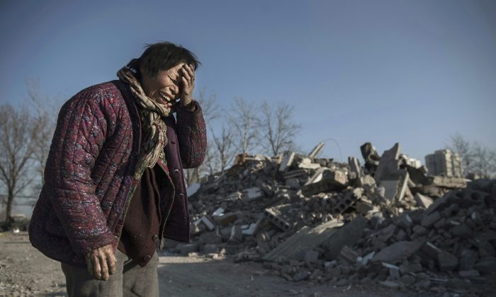 Woman in front of her destroyed house