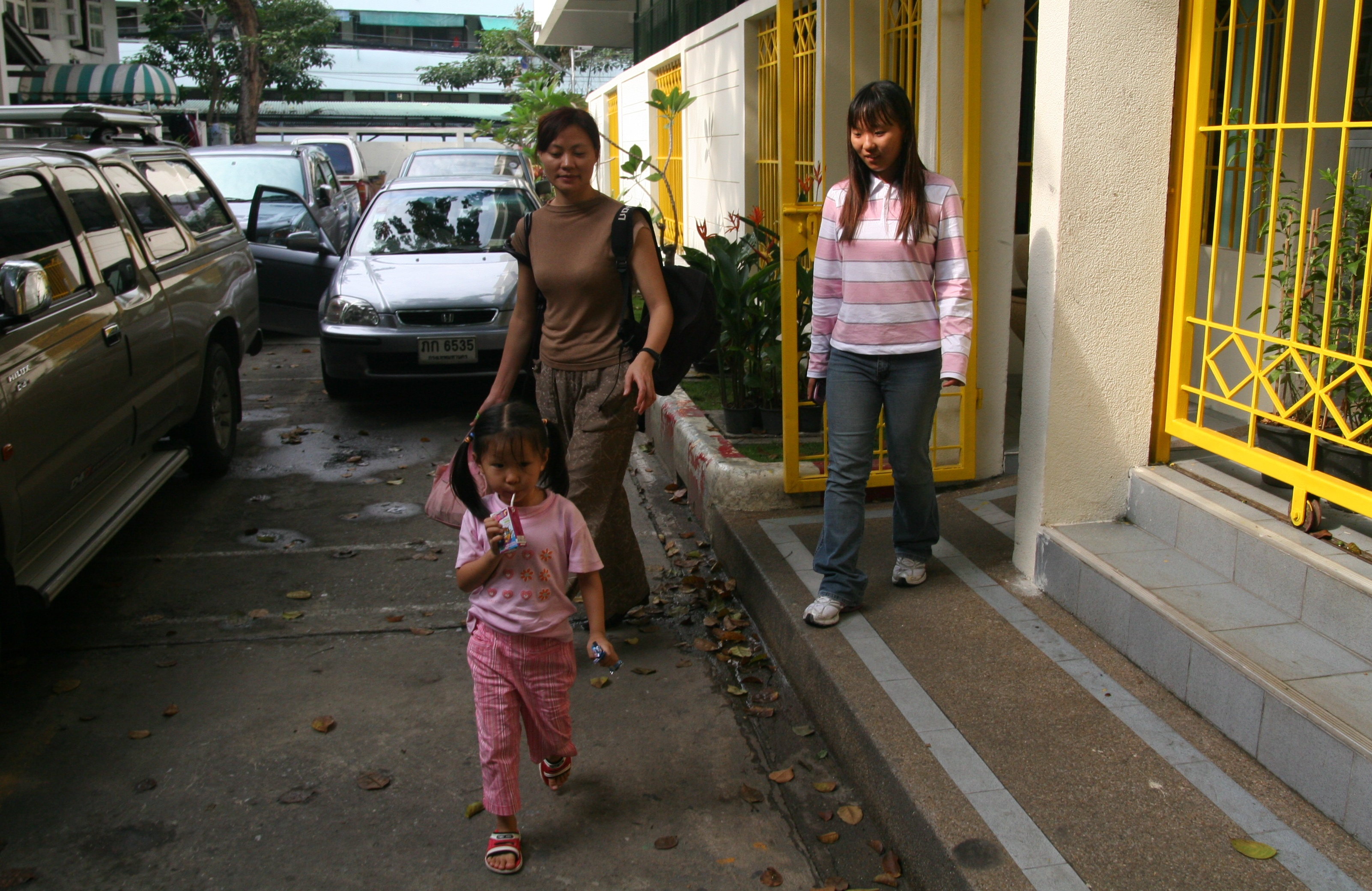 Four-year-old Huang Ying leaves the Immigration Detention Center (IDC) in Bangkok, with a family friend and 14-year-old Wang Anqi, whose parents are still incarcerated and had their visas to Thailand cancelled. They are appealing the decision. (The Epoch Times)