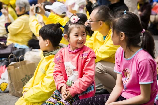 Little girls react after watching the Falun Dafa dragon dance team perform. (Samira Bouaou/The Epoch Times)