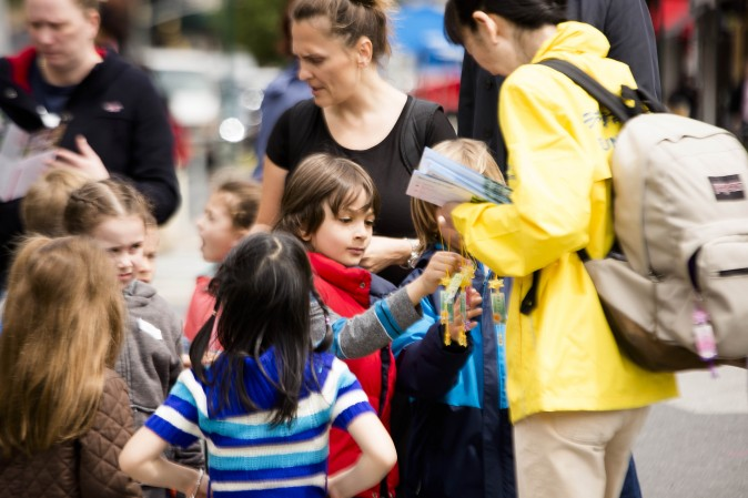 A Falun Dafa practitioner distributes origami lotus flowers to children during the World Falun Dafa Day event at Union Square, New York City, on May 11, 2017. (Samira Bouaou/The Epoch Times)