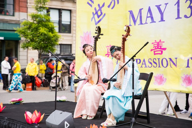 Jia Ge and Le Le play the Chinese traditional pipa instrument during the World Falun Dafa Day event at Union Square, New York City, on May 11, 2017. (Benjamin Chasteen/The Epoch Times)