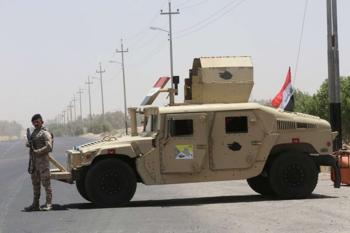 An Iraqi soldier stands next to a military vehicle