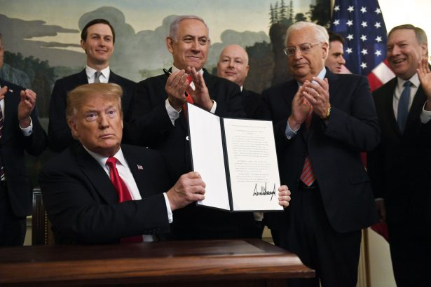 President Donald Trump holds up a signed proclamation