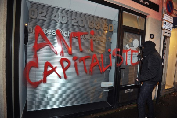A member of the Antifa extremist group vandalizes a storefront in Nantes, France, on Feb. 14, 2014. (FRANK PERRY/AFP/Getty Images)