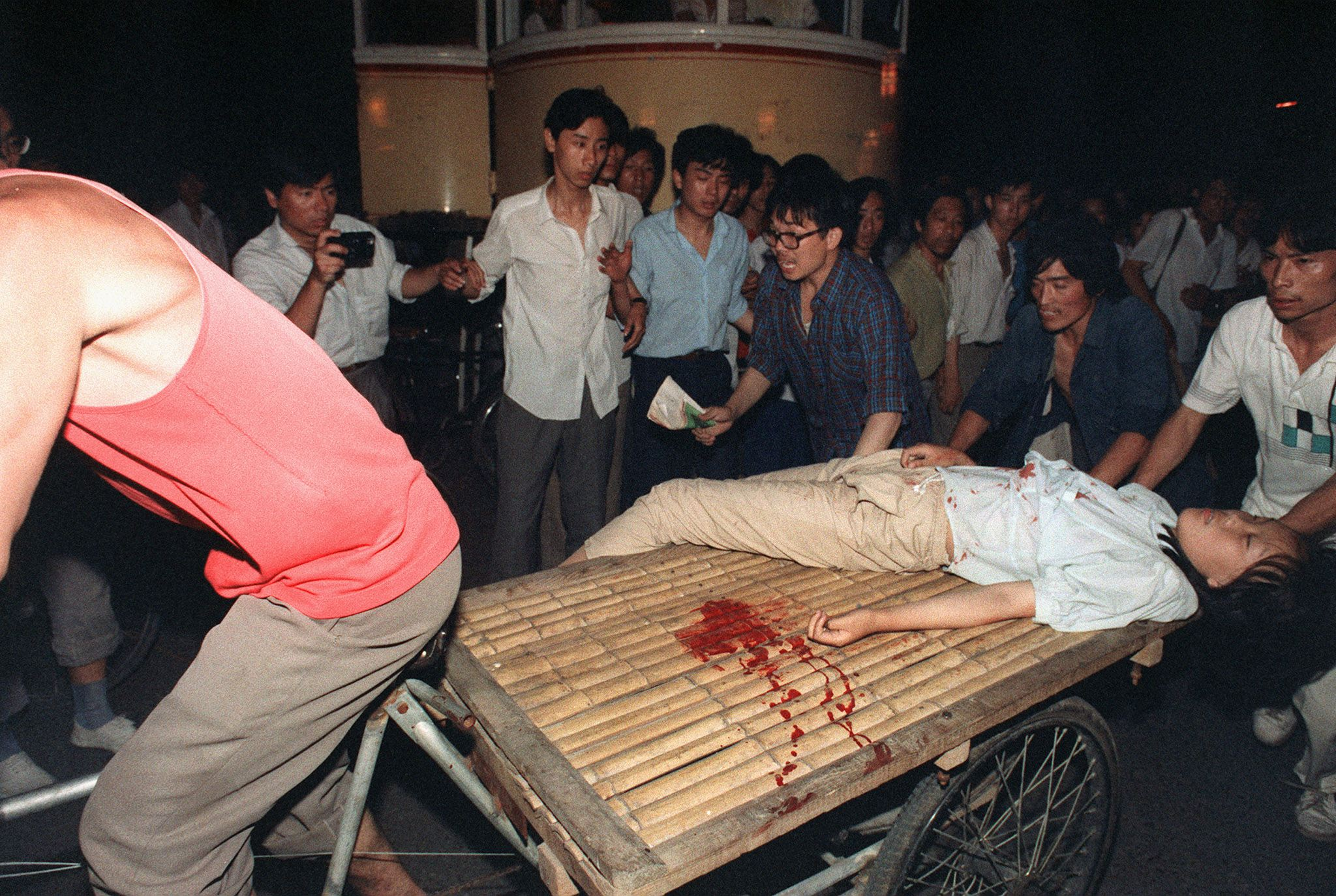 A girl wounded during the clash between the army and students 04 June 1989 near Tiananmen Square is carried out by a cart (MANUEL CENETA/AFP/Getty Images)