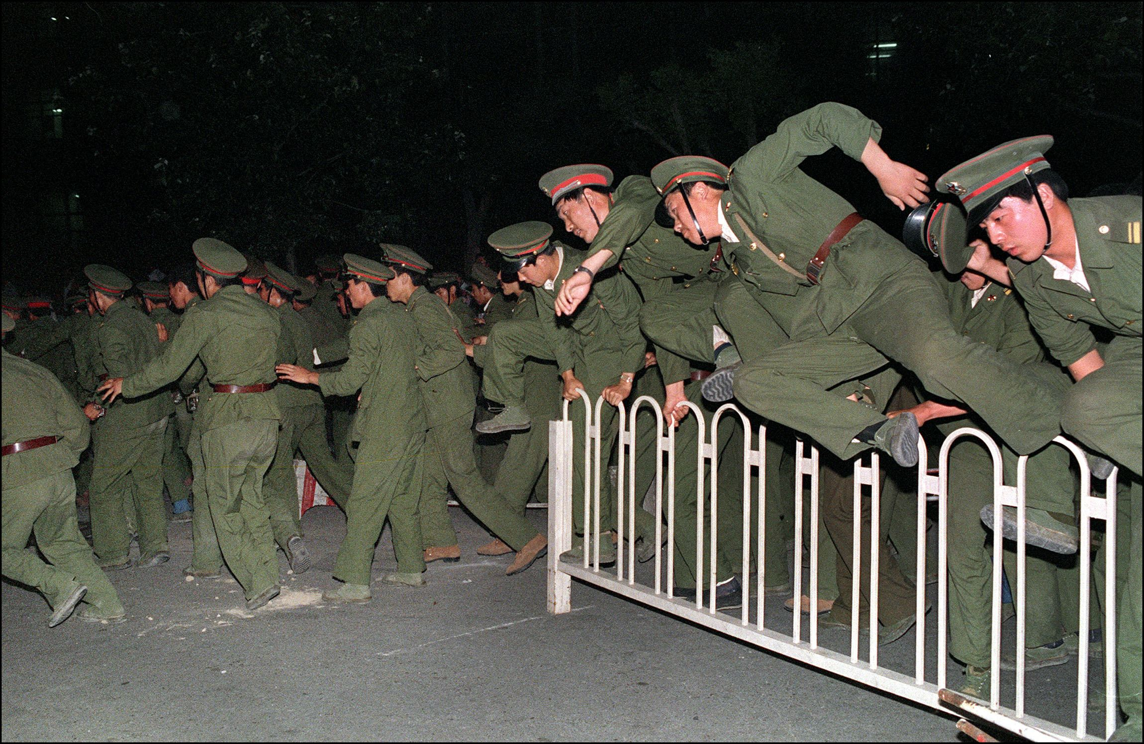 People Liberation Army (PLA) soldiers leap over a barrier on Tiananmen Square in central Beijing 04 June 1989. (CATHERINE HENRIETTE/AFP/Getty Images)