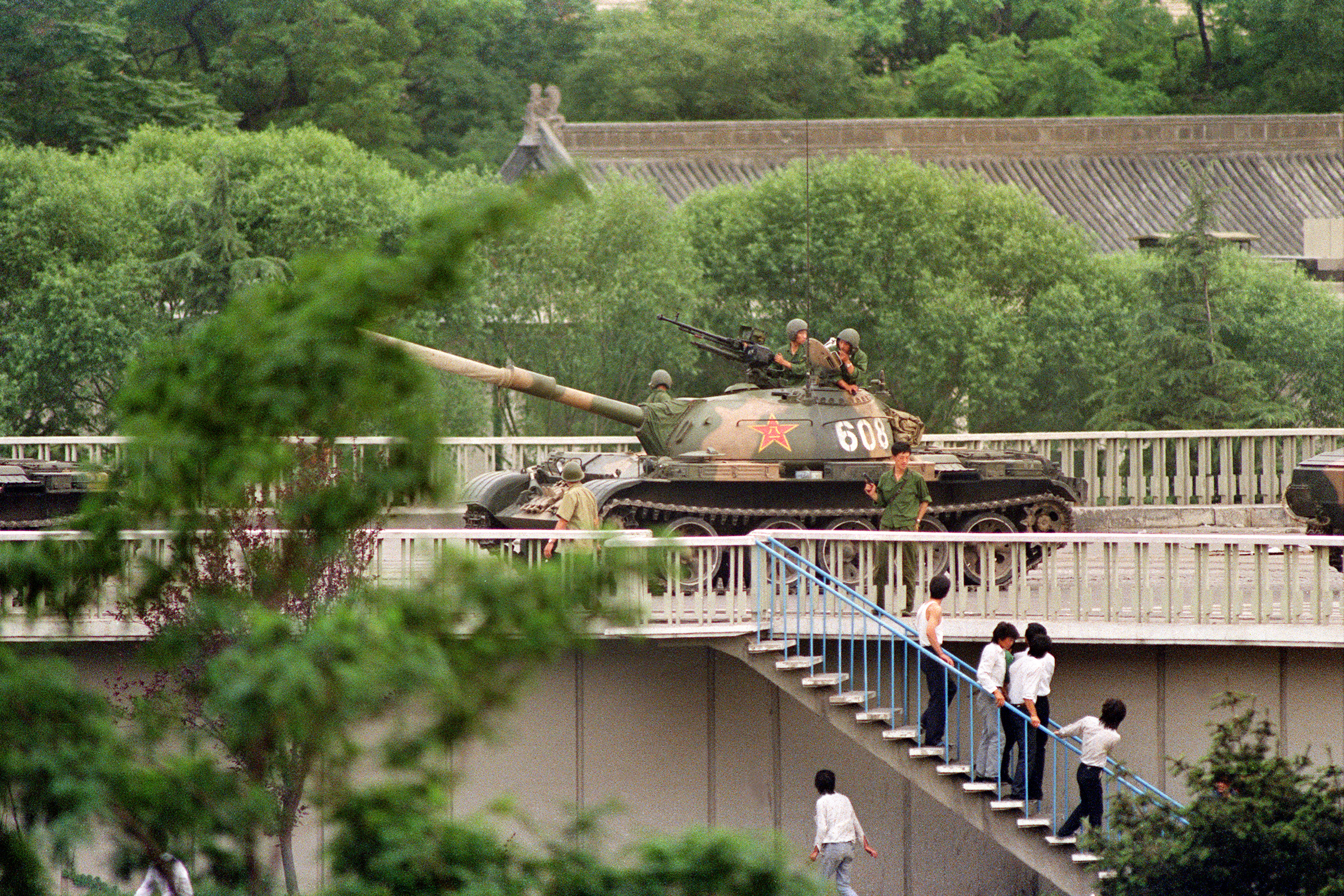 Chinese onlookers run away as a soldier threatens them with a gun on June 5, 1989. (CATHERINE HENRIETTE/AFP/Getty Images)