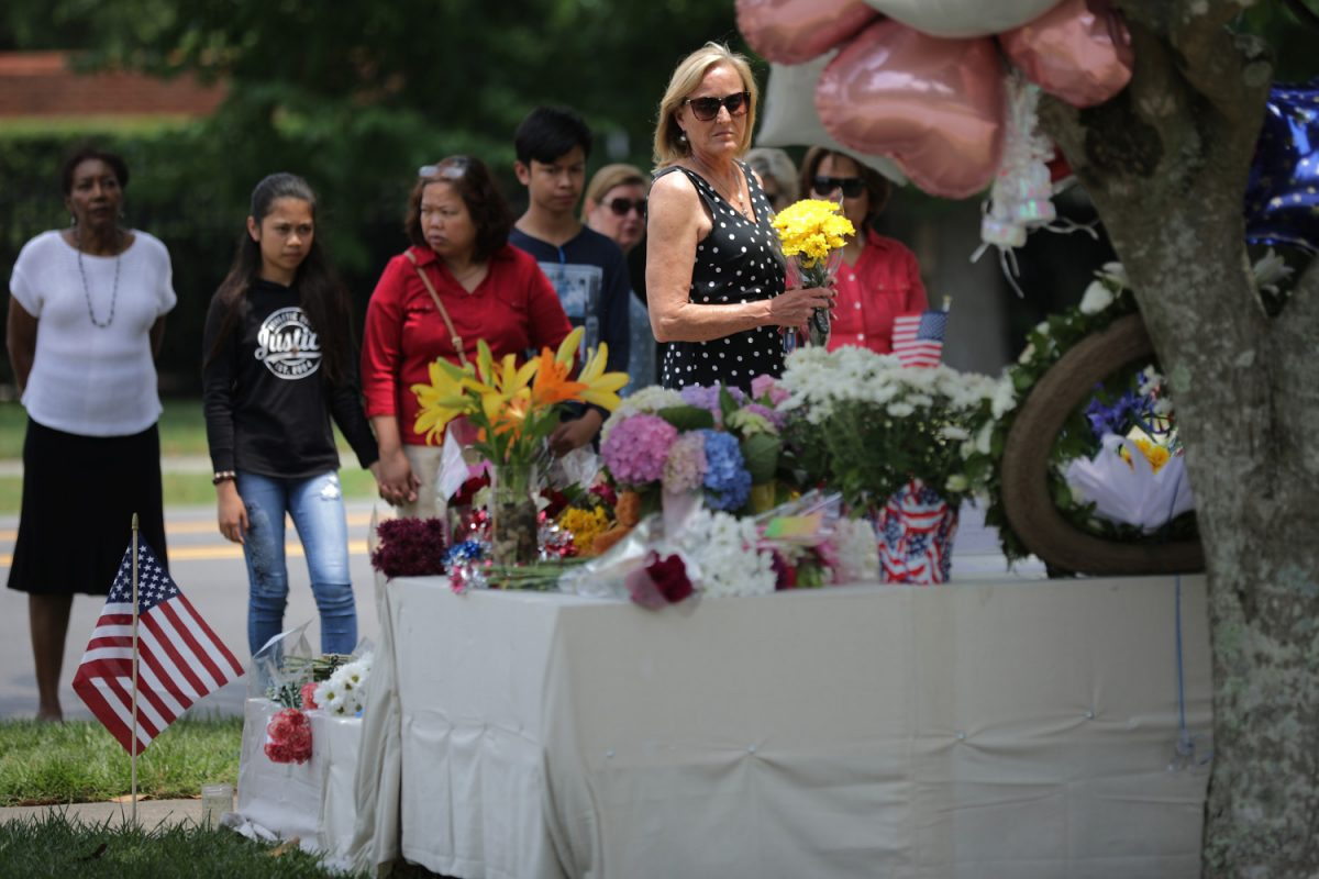 People place flowers at a makeshift memorial