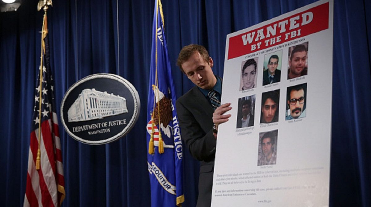 A Department of Justice employee put up a poster of the seven indicted hackers prior to a news conference