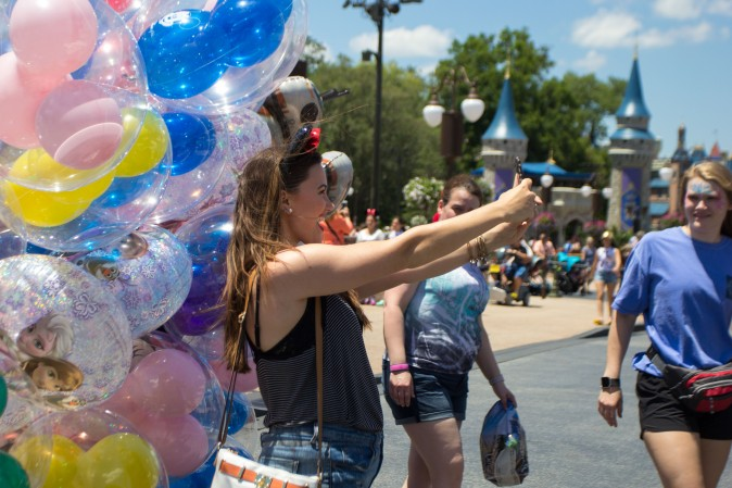 A woman takes a selfie with Mickey Mouse shaped balloons at the Magic Kingdom park in Orlando on May 22, 2016. (Benjamin Chasteen/Epoch Times)