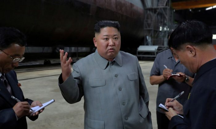 North Korean leader Kim Jong Un, center, speaks while inspecting a newly built submarine to be deployed soon, at an unknown location in North Korea. (Korean Central News Agency/Korea News Service/File Photo via AP)