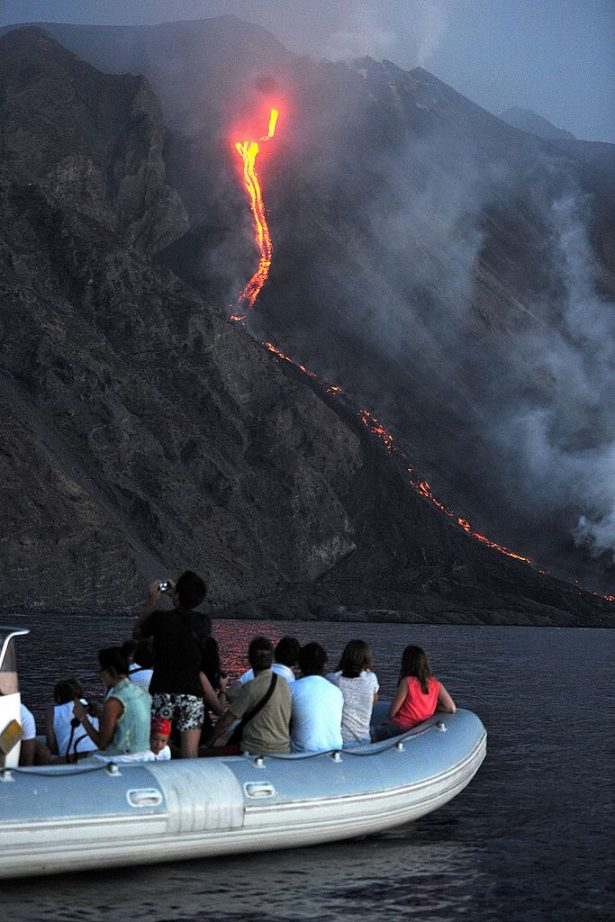 A boat of tourists watches as lava from the Stromboli volcano