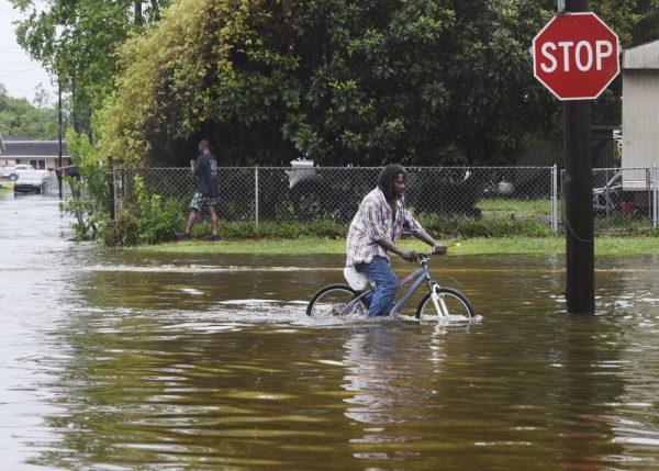 A man tries to bike through the flooding