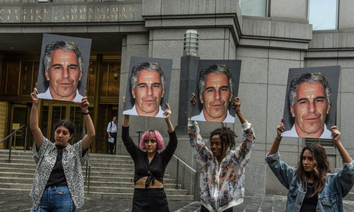 "A protest group called ""Hot Mess"" hold up signs of Jeffrey Epstein in front of the Federal courthouse on July 8, 2019 in New York City. (Stephanie Keith/Getty Images)"