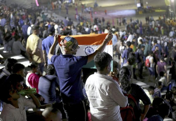 An Indian spectator folds a flag as others leave