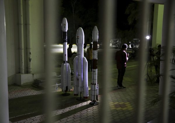 An Indian Video journalist reports standing next to models of Indian Space Research Organization (ISRO)'s Geosynchronous Satellite launch Vehicle