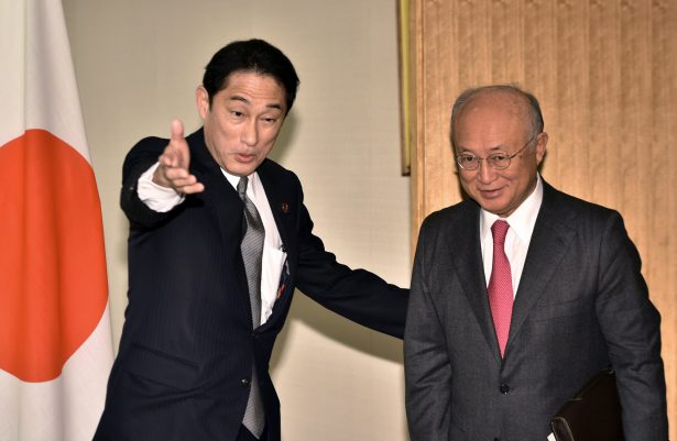 Yukiya Amano (R), director general of the International Atomic Energy Agency (IAEA) is greeted by Japanese Foreign Minister Fumio Kishida