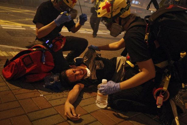 Medical workers help a protester in pain from tear gas fired by policemen