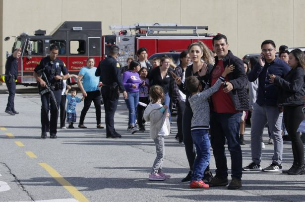 Shoppers hug after being escorted from the Tanforan Mall