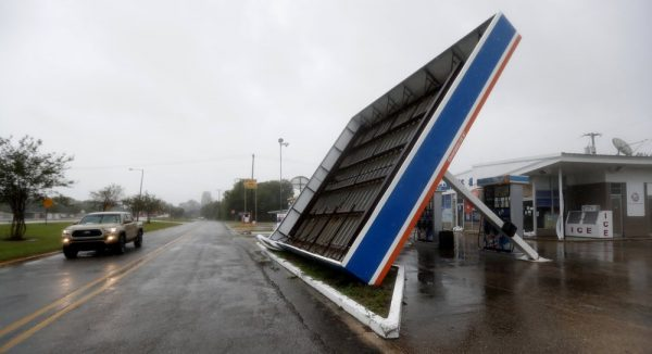 A vehicle passes a toppled gas pump canopy in Berwick