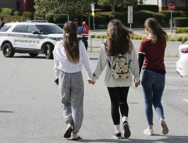 Three teens hold hands after being escorted