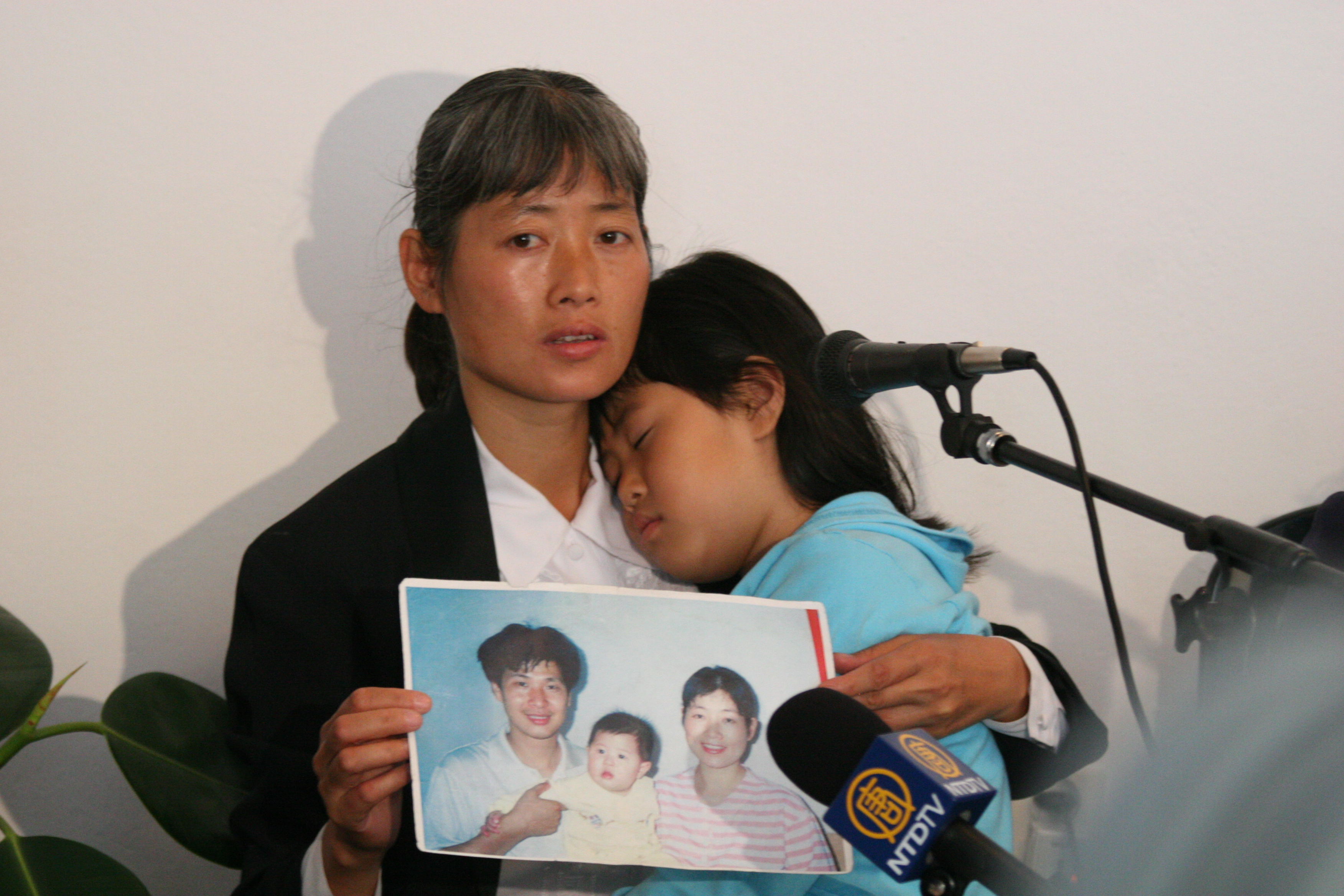 "PAIN LINGERS: Ms. Zhizhen Dai, panelist at the ""Never Again: Appeal to the World"" forum discussing illegal organ harvesting in death camps in China, speaks of the 2001 torture and murder of her husband at the hands of Chinese authorities. Her daughter Fadu naps in her arms. The forum was held in Auschwitz, Poland on May 9, 2006. (Jan Jekielek/The Epoch Times)"